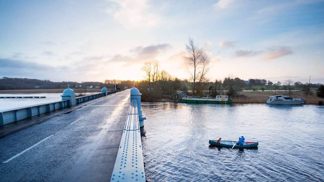 Woman paddling a canoe under Portumna Bridge in Galway with a dog sitting at the front