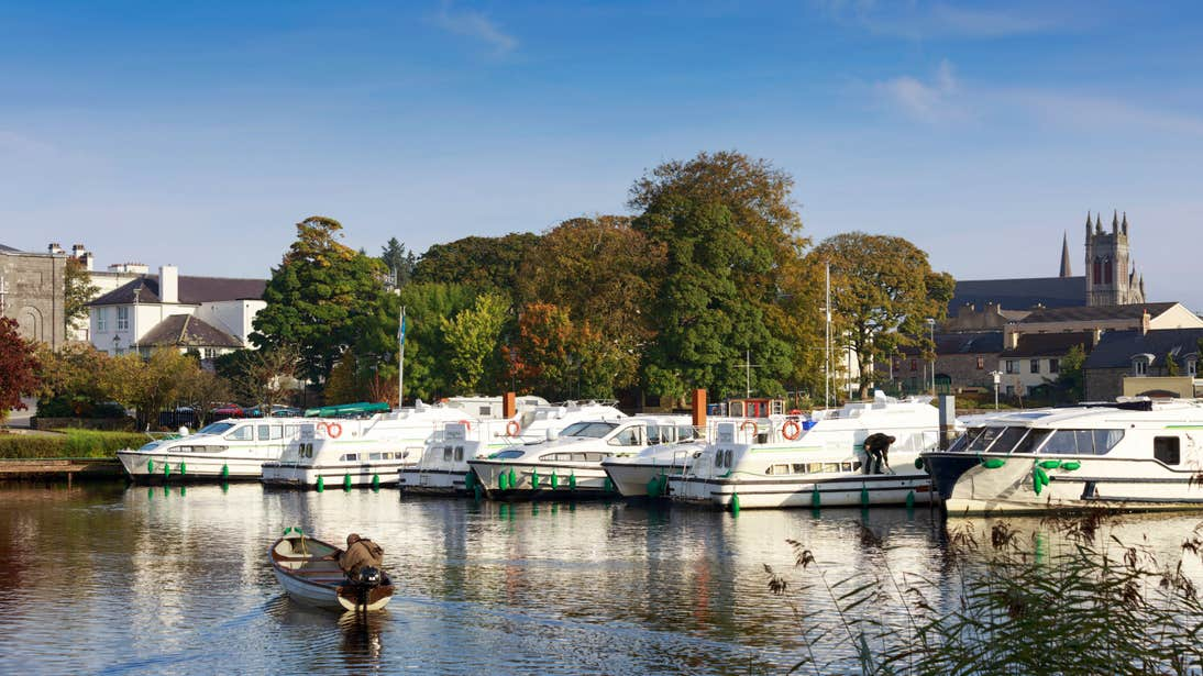 Boats in a marina with a backdrop of trees and a church in Carrick-on-Shannon, Leitrim