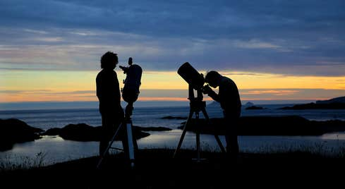 Two people looking up at the sky through telescopes in Dark Sky Park, Kerry