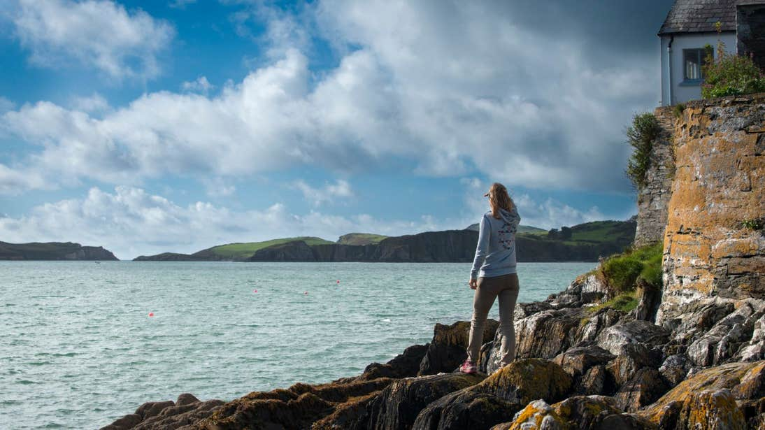 A woman looking out at the still waters and blue skies from Castletownshend Harbour