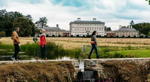 Three people walking on a path in front of Castletown House, Co Kildare