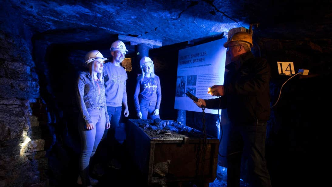 Four people hard hats on an underground tour in the Arigna Mines in Roscommon.