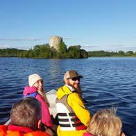 Group of people in a boat with lake shore and castle in the background