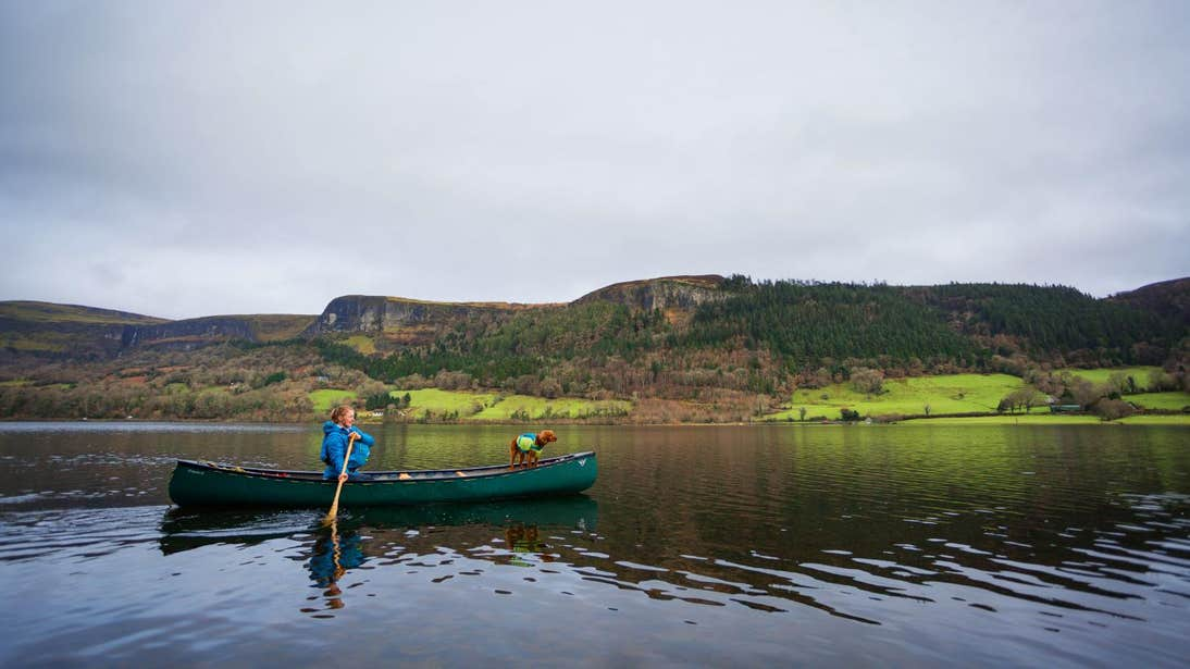 Woman and a dog on a canoe in Glencar Lake, Leitrim