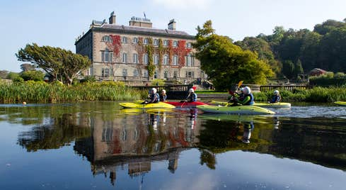 Group of people kayaking on the water in front of Westport House, County Mayo.