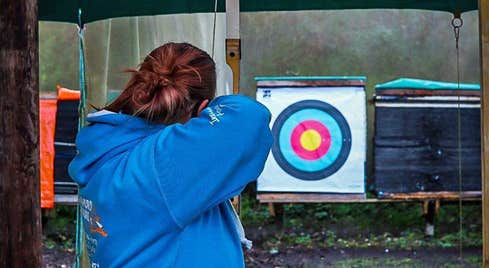 A person aiming at an archery target at Skypark in Carlingford