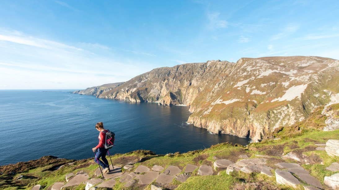 A woman walking across the Slieve League sea cliffs with an amazing view of the Atlantic Ocean
