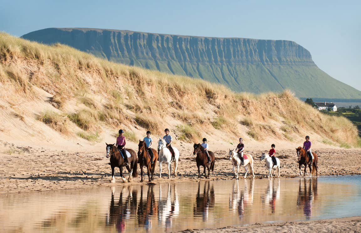 People horse riding on the beach in County Sligo