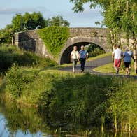 Two couples walk past each other on the Royal Canal Greenway near a stone bridge