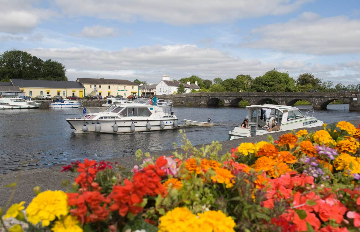 Boats cruising on the River Shannon with a backdrop of beautiful flowers