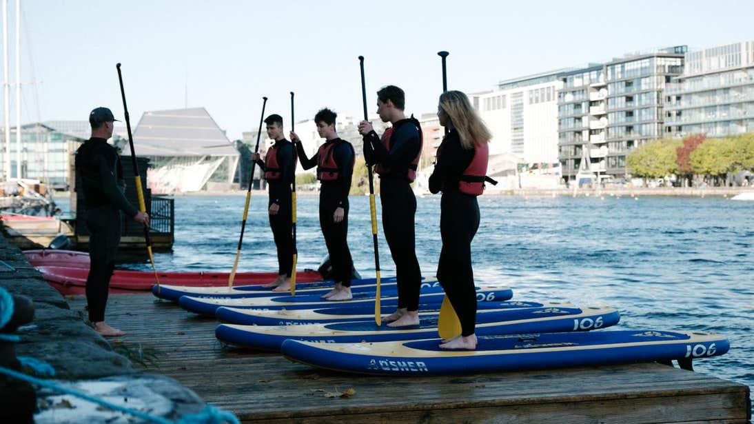 People standing on paddle boards at Grand Canal Dock in Dublin.
