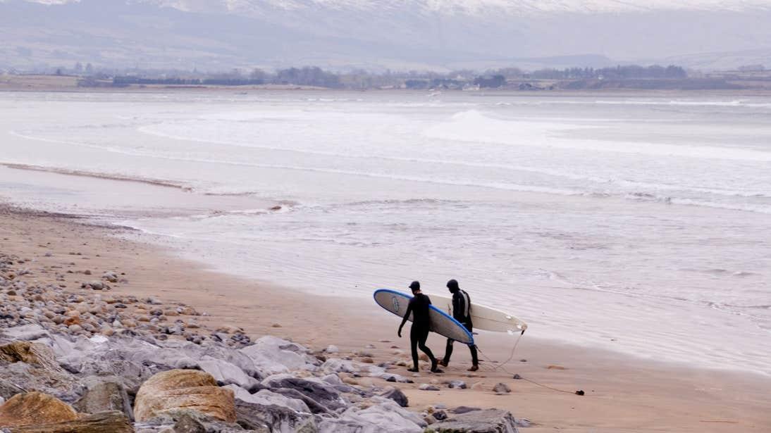 Two surfers walking along Strandhill Beach in Sligo holding their boards