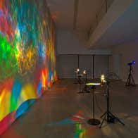 Colourful light show projected on a wall in a gallery