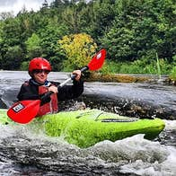 A lone kayaker rushing down small rapids on a river surrounded by trees
