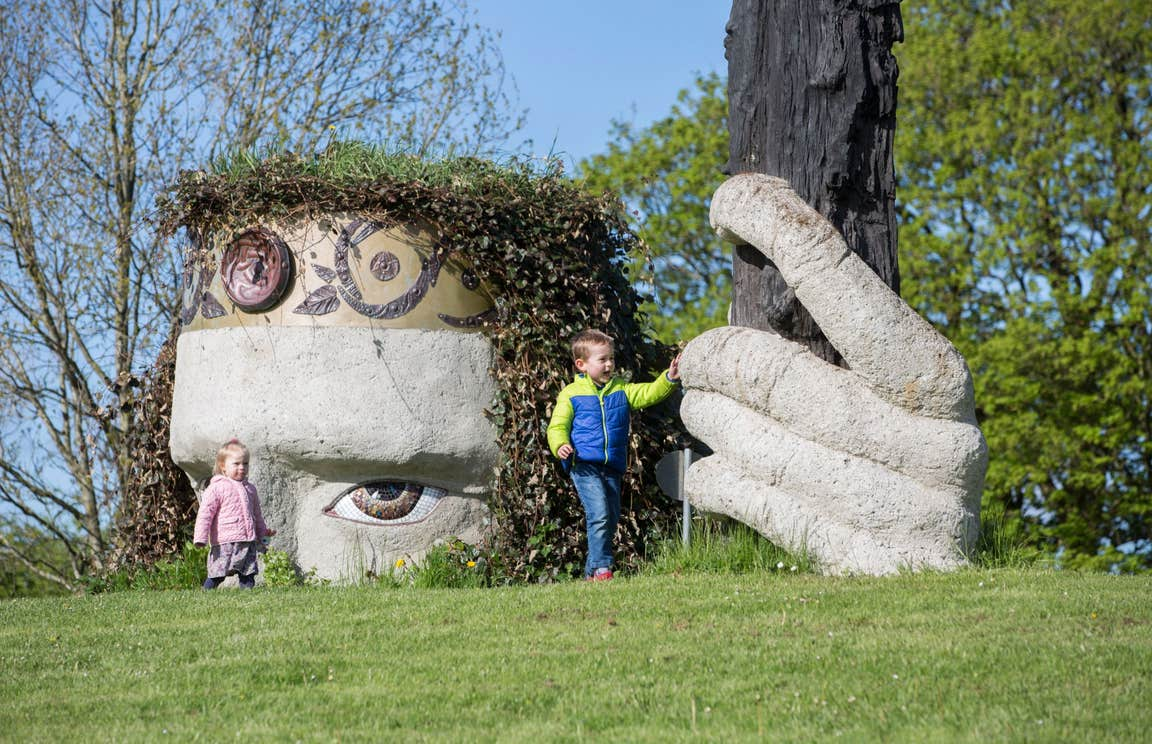 Two Kids playing at Dun na Si Westmeath beside some large sculptures