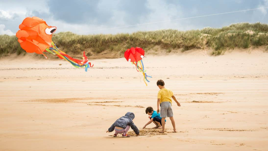 Three children flying colourful kites on Marble Hill Beach