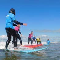 Kids on surf boards taking surfing lessons with an instructor in shallow waters