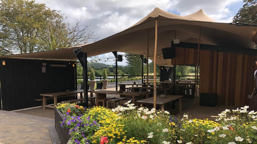A large outdoor marquee surrounded by flowers at The Anglers, Carrigrohane, Cork