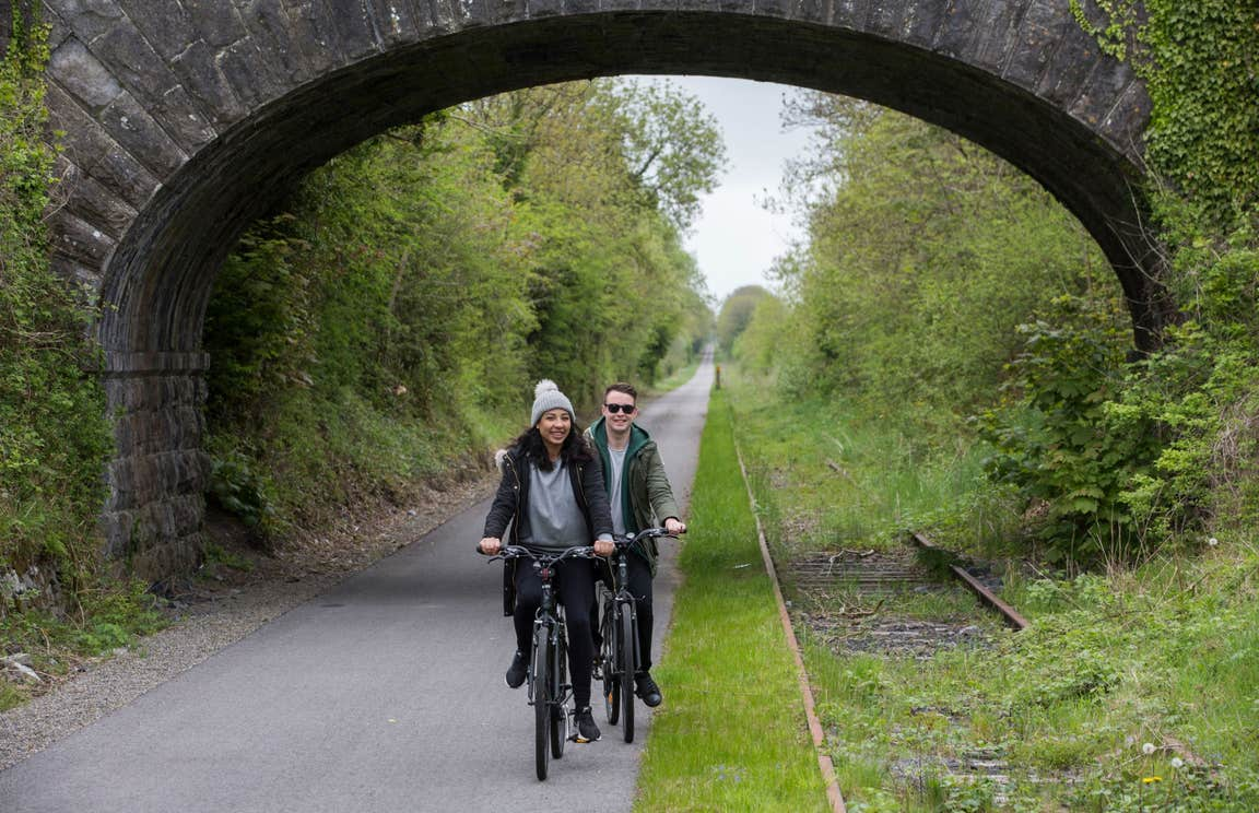Two people cycling under a stone bridge on a cycle path in Westmeath