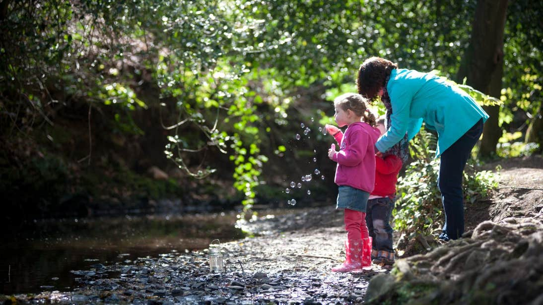 Mother and children blowing bubbles by a river