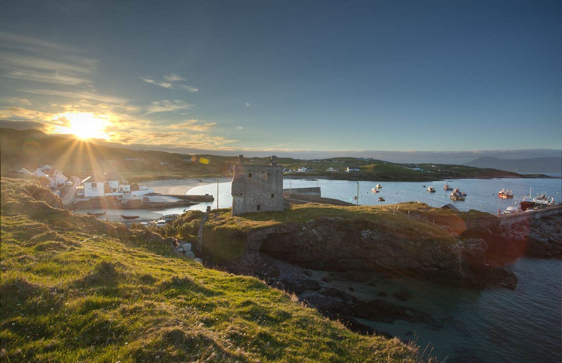 A view of the sun over Clare Island, Mayo with boats bobbing on the water in the background
