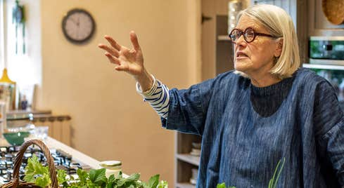 A view of Darina Allen with her right hand raised giving a talk to unseen people as she stands in front of kitchen counter with fresh herbs on display as well as a gas hob on the left hand side of the picture