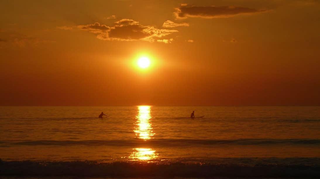 Two surfers paddling in the ocean at sunset in Strandhill, Sligo