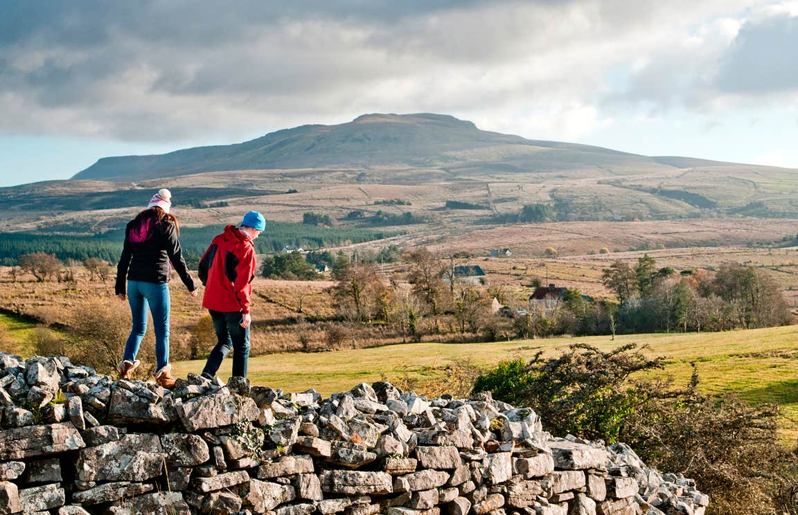 Two people walking on a stone wall in Cavan Burren Park, Cavan