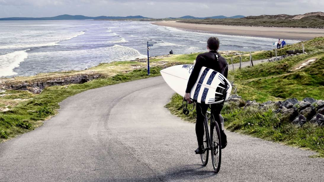 Surfer riding his bike to the beach to go surfing in Bundoran, Donegal
