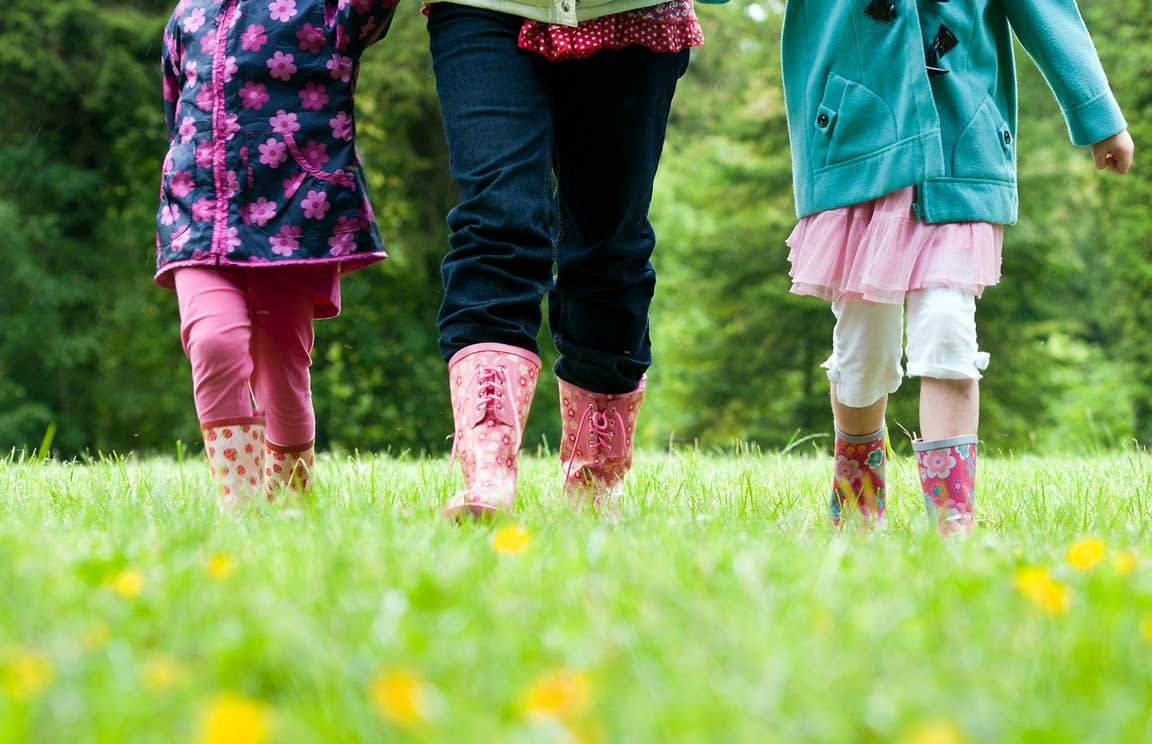 Two children and one adult wearing wellington boots walking in a field of green grass filled with buttercups