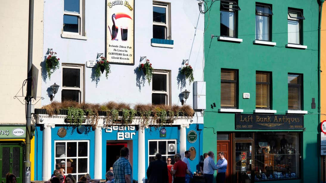 People standing outside Sean's Bar on a sunny day in Athlone, Westmeath