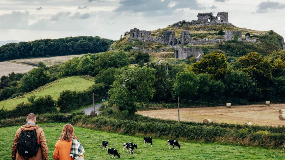 A couple walking towards the ruins at the Rock of Dunamase, Laois