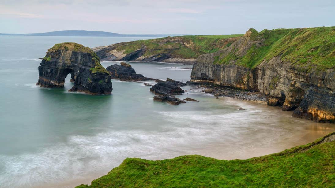 Calm waters and grass covered cliffs at Ballybunion in Co. Kerry.