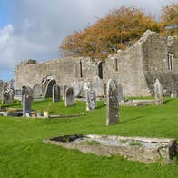 The ruins of a church with some ancient headstones scattered amongst green grass