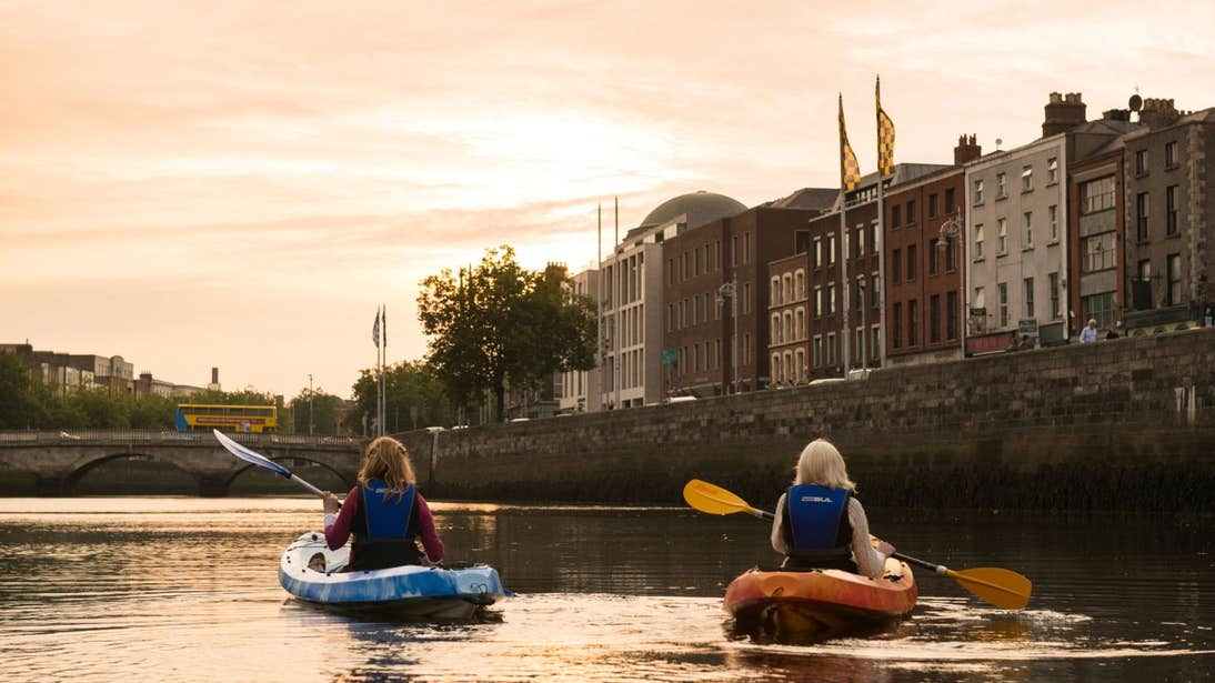 Two girls kayaking down the River Liffey in Dublin City at sunset