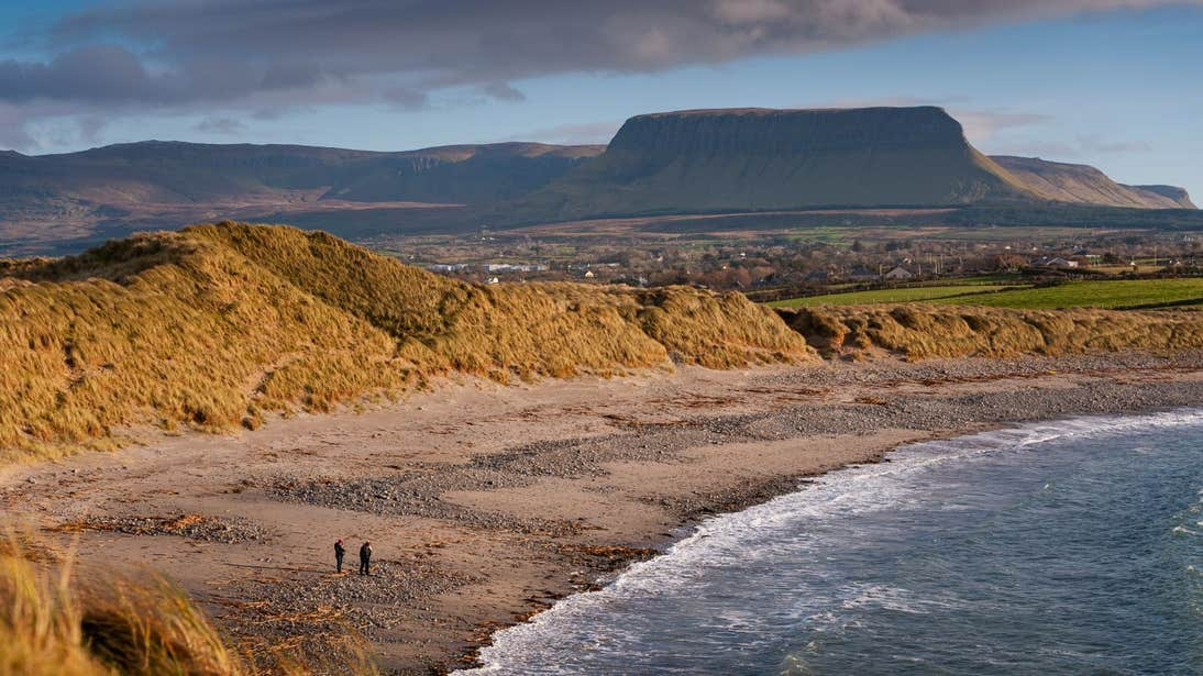 Two people walking Streedagh Beach, Co Sligo with Benbulben in th background.