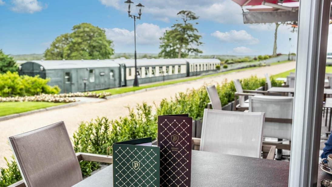Dining tables and chairs in front of a railway carriage at Glenlo Abbey Hotel and Estate, Galway.