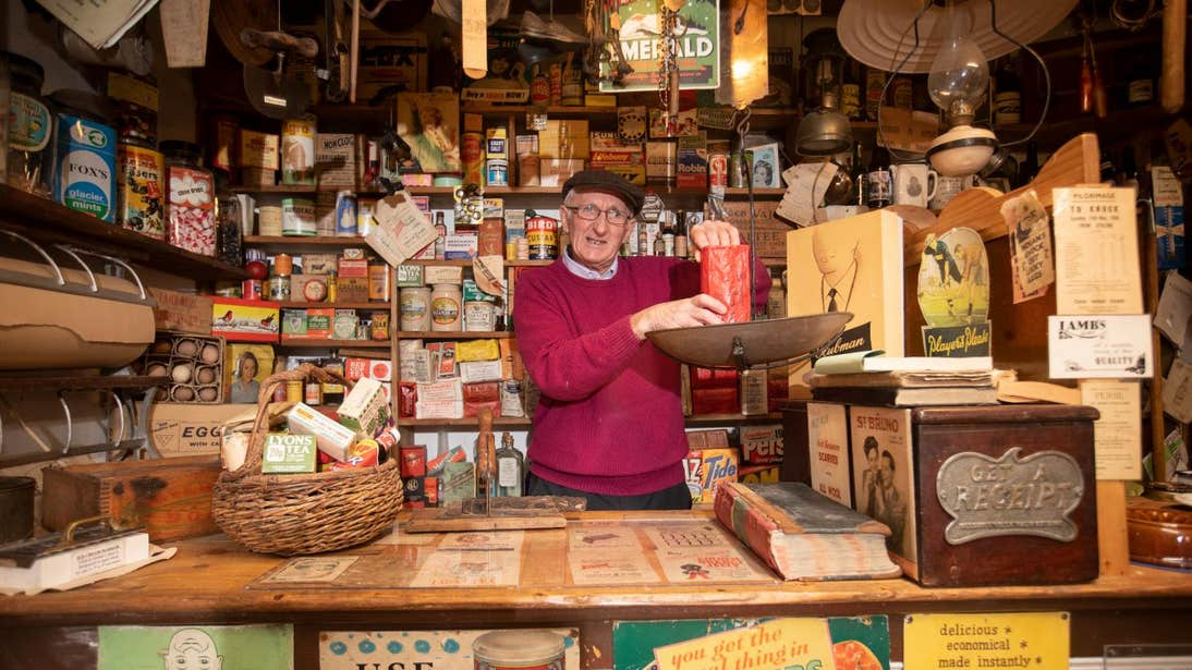 Man standing behind a counter weighing ingredients at Derryglad Folk and Heritage Museum in Roscommon