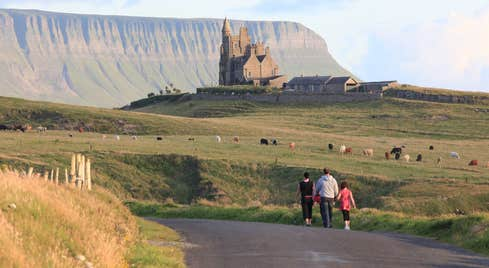 Three people walking on Mullaghmore Head, Sligo with Classiebawn Castle in the distance