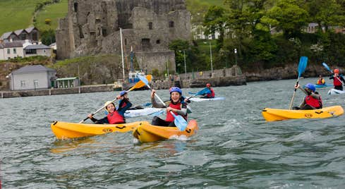 Kids kayaking in yellow kayaks in front of a castle in Louth