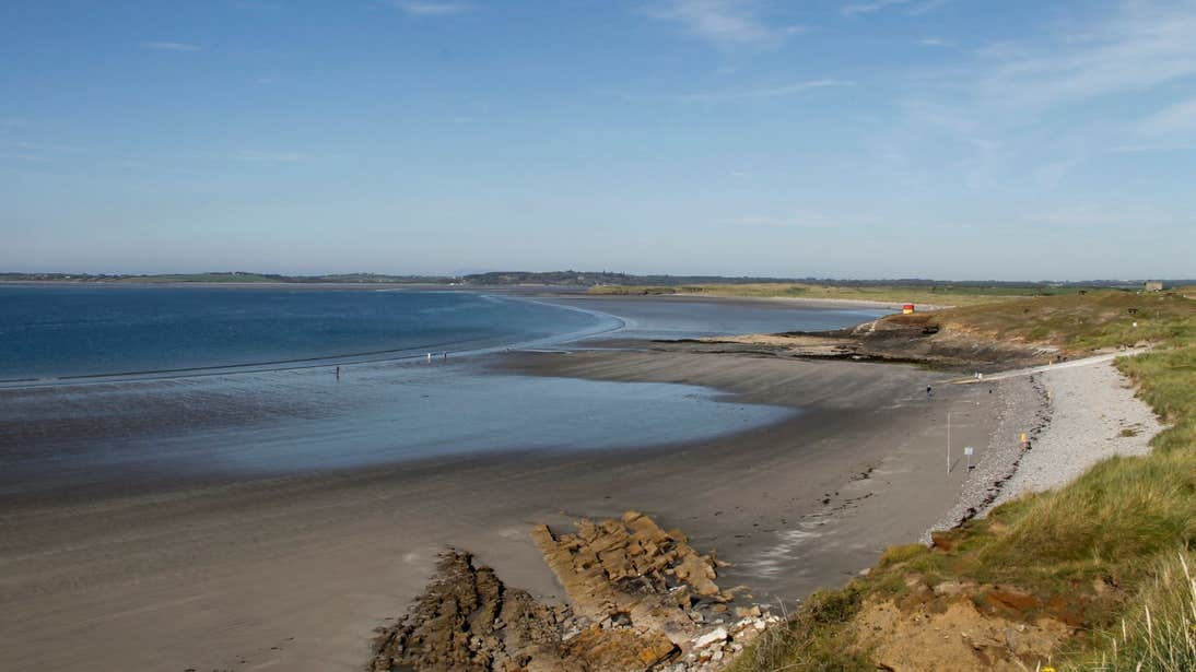 Still blue water and sand dunes at Rosses Point, Sligo