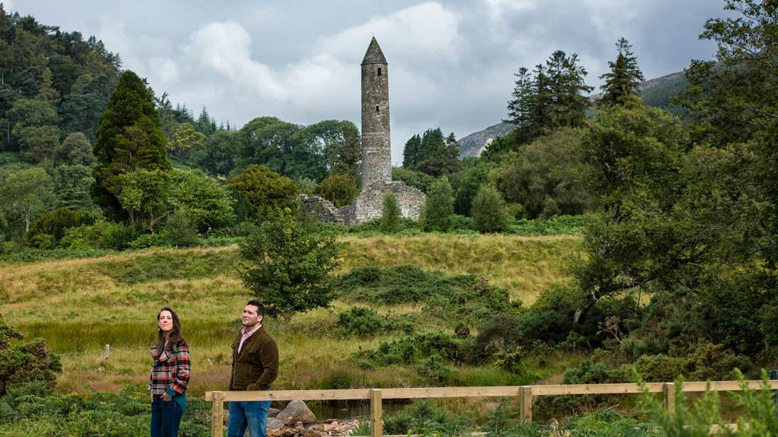 People walking past a round tower in Glendalough, Wicklow