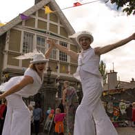 Two performers on stilts outside Birr Theatre during an Arts event