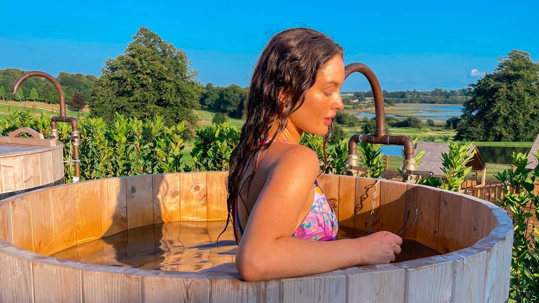 Roz Purcell in a wooden hot tub at sunset at Wineport Lodge in Athlone, Westmeath