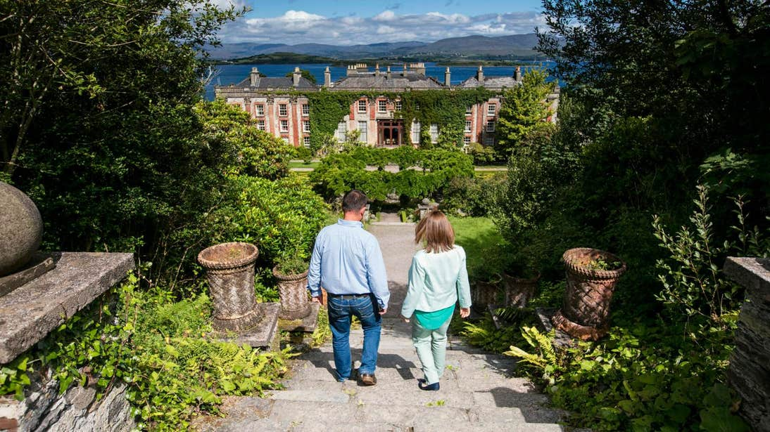 Couple walking down steps towards Bantry House and Gardens, Cork