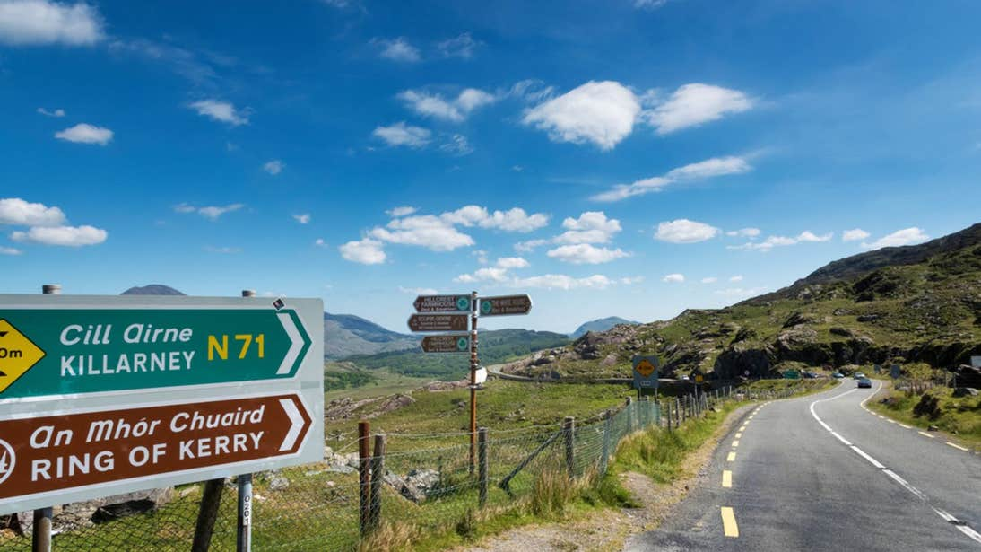 Signpost at the Ring of Kerry on a sunny day with hills in the distance