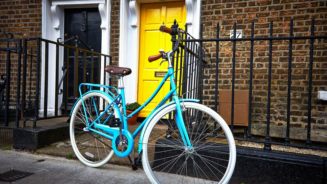 A blue bicycle outside a yellow door in Dublin City Centre