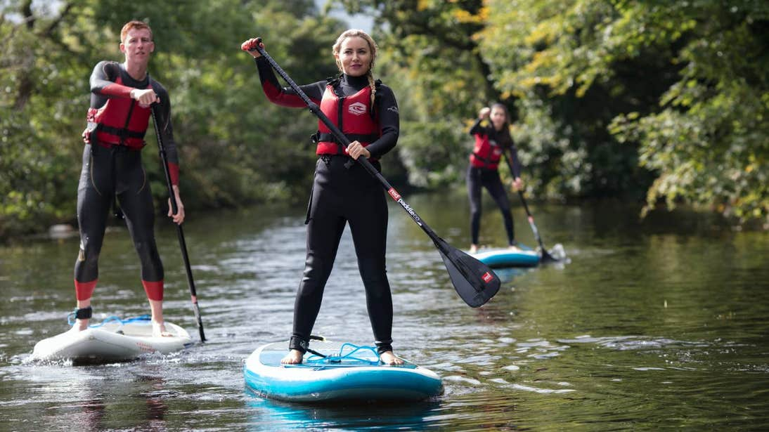 Three people stand-up paddle boarding across a waterway.