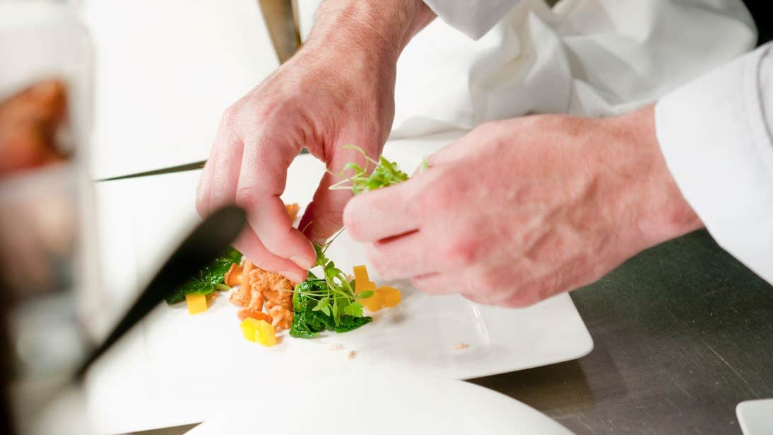 Chef plating food on a square, white, plate
