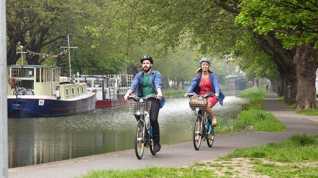 A man and a woman cycling along the Grand Canal, Dublin with boats in the background.
